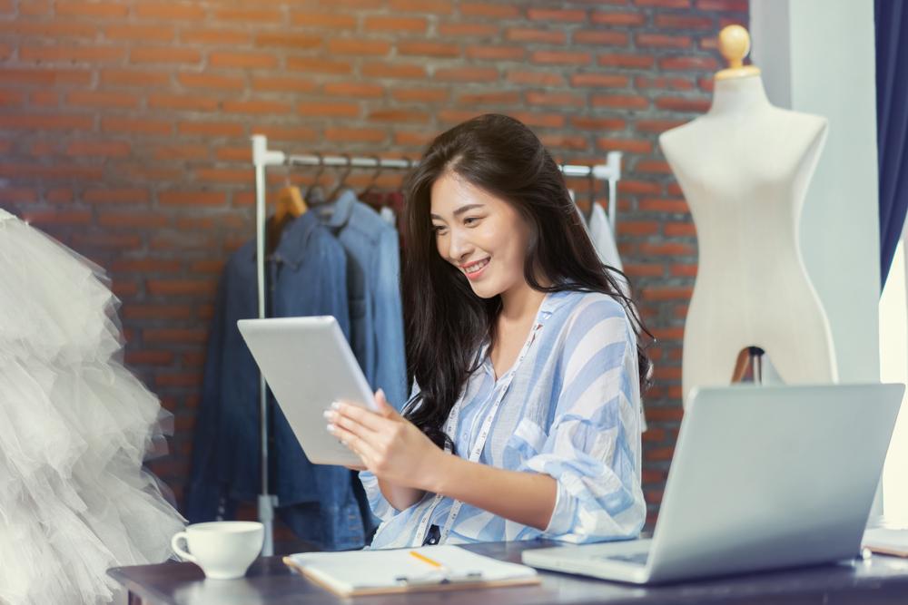 Jovem designer de moda interagindo com tablet e laptop, realizando empreendedorismo digital.