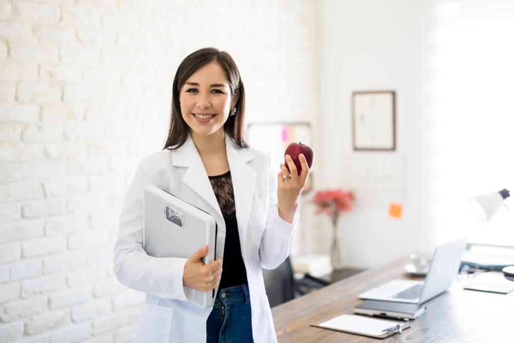 Profissional graduada em uma faculdade de Nutrição segurando uma maçã e uma balança