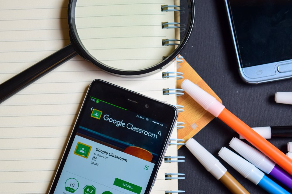 Celular sobre caderno, com aplicativo do Google Classroom aberto