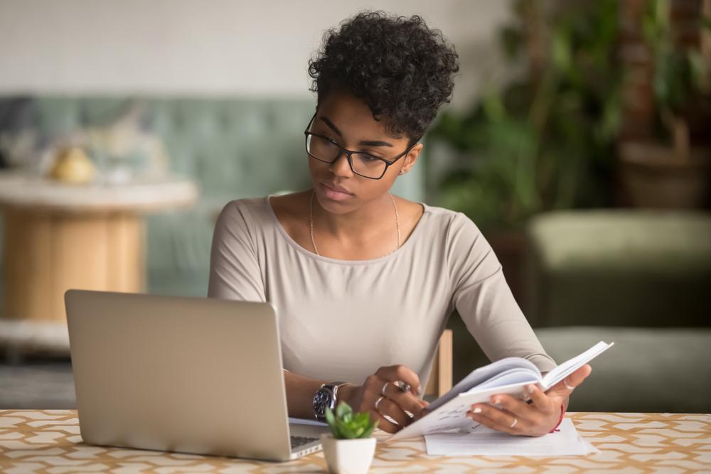Jovem mulher estudante com livro na mão, de frente a um laptop, cheia de foco nos estudos