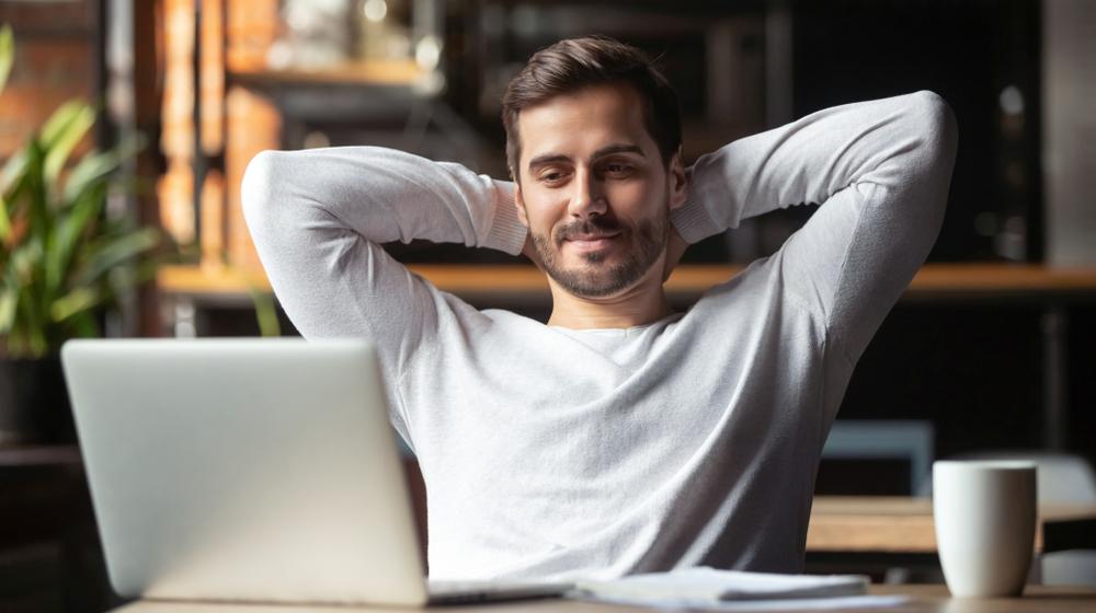 Homem que aprendeu a relaxar e estudar, de frente para o computador, em uma cafeteria.