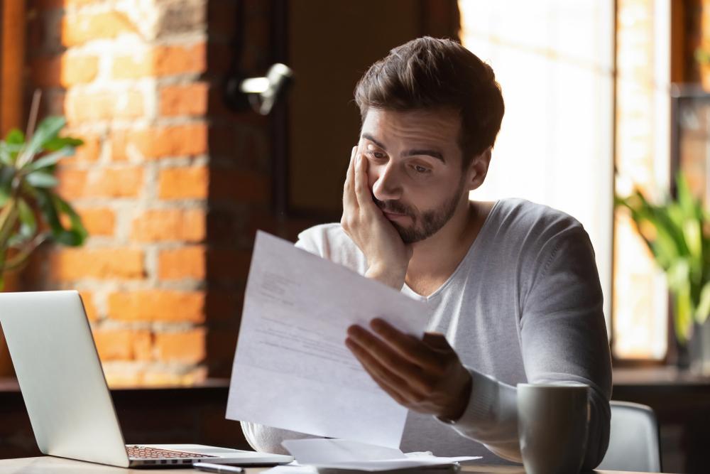 Homem jovem segurando uma prova com uma mão e apoiando o rosto sobre a outra, demonstrando preocupação com as notas da faculdade.
