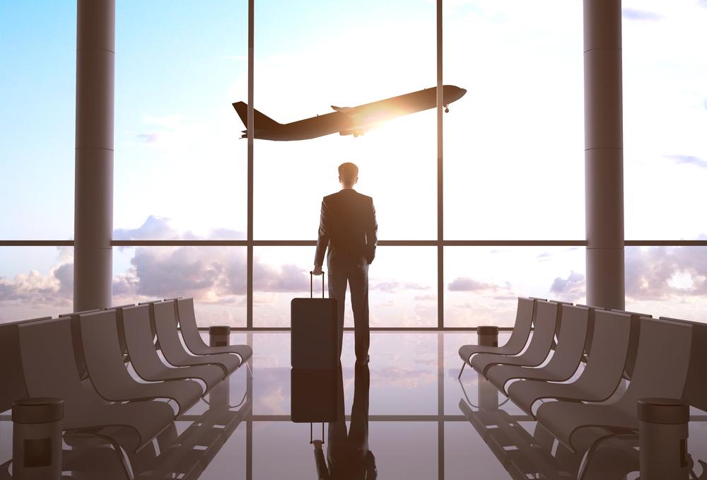 Profissional de malas prontas em um aeroporto olhando um avião e imaginando sua carreira no exterior