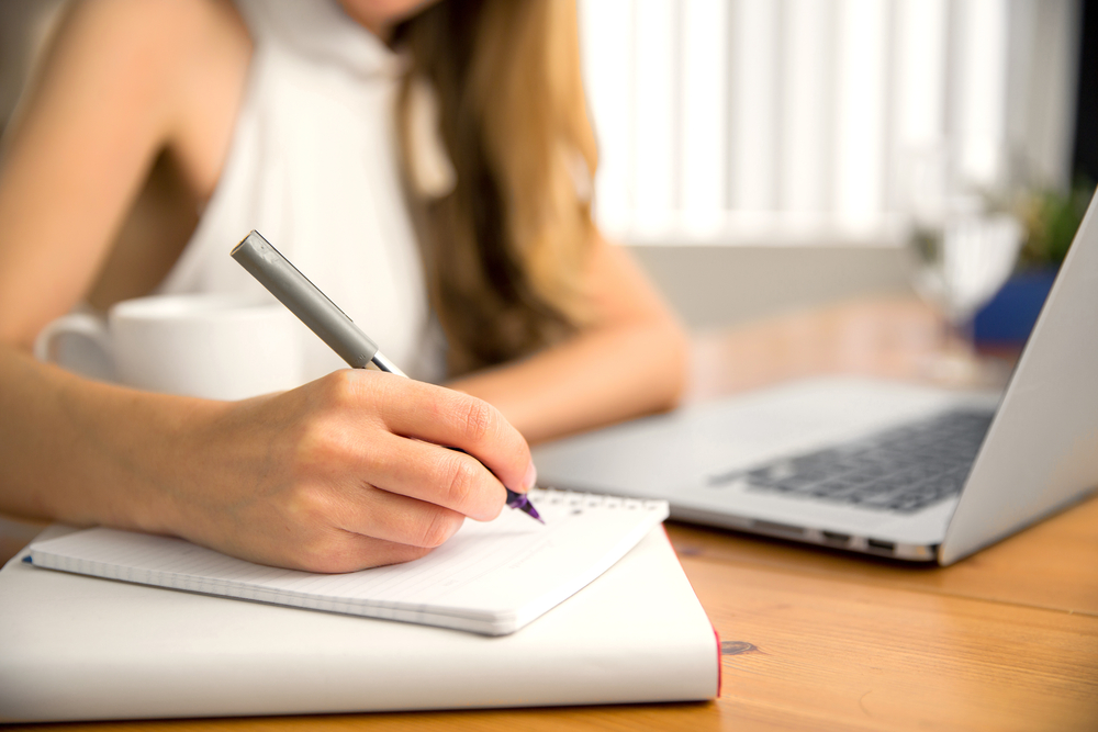 Garota estudante fazendo anotações em um caderno, referentes ao seu plano de estudos