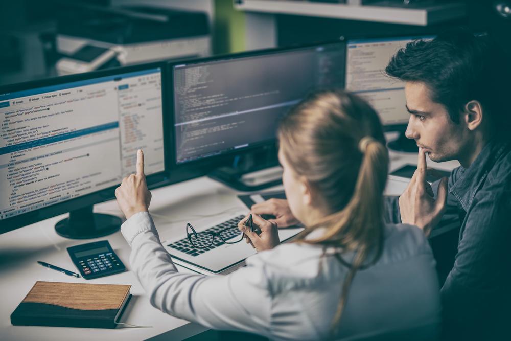 Profissionais de Análise e Desenvolvimento de Sistemas durante o trabalho