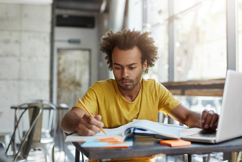 Jovem estudando organizadamente para melhorar seu desempenho na graduação