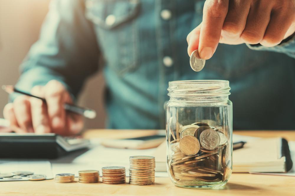 Homem colocando moedas em um pote para economizar durante a faculdade